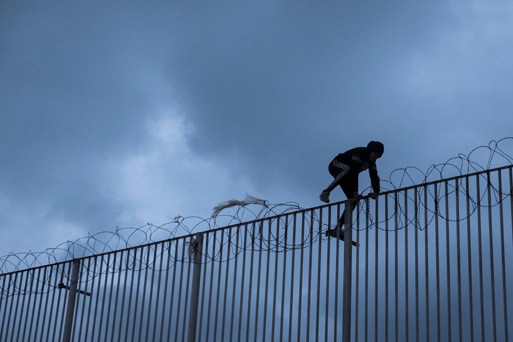 Un menor salta la valla en Ceuta. Foto: Pedro Armestre / Save the Children.
