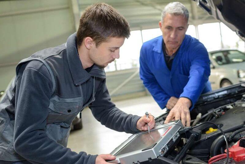 Dos personas de diferentes edades trabajando en el sector de la automoción