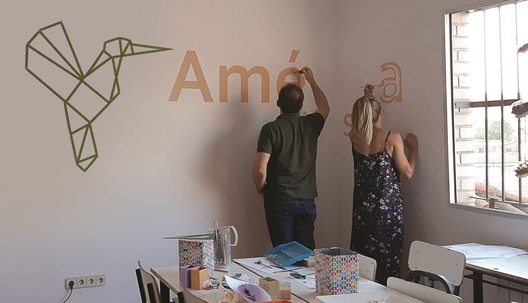 Dos empleados de Aecom trabajan como voluntarios decorando una pared