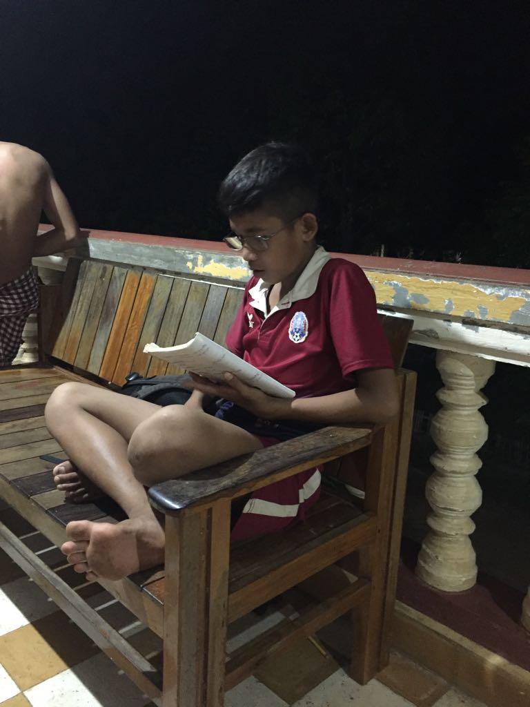 Niño leyendo con gafas donadas.