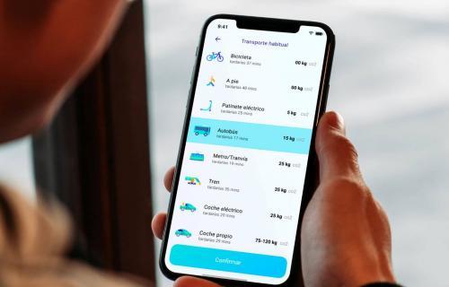 Una persona consulta información relativa al transporte habitual en su dispositivo móvil