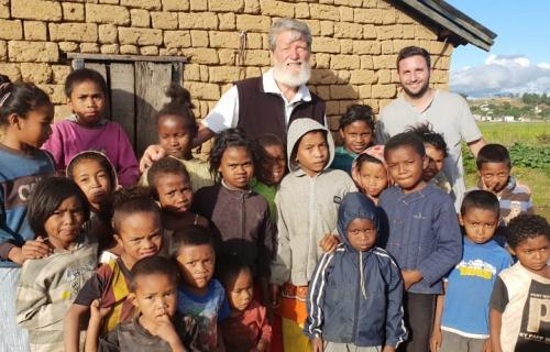 El padre Pedro Opeka y Gastón Vigo junto a un grupo de niños de Akamasoa