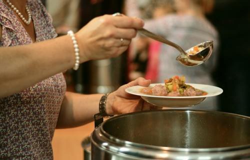 Una mujer sirviendo alimentos en un comedor social