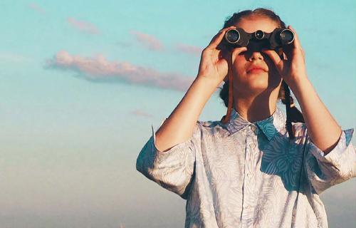 Una niña otea el horizonte a través de unos prismáticos.