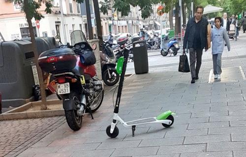 Un patinete mal aparcado en medio de una acera de Madrid
