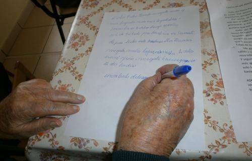 Una mujer mayor en aislamiento contesta a una carta de un voluntario.