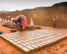 Mujer africana en una fábrica de ladrillos.